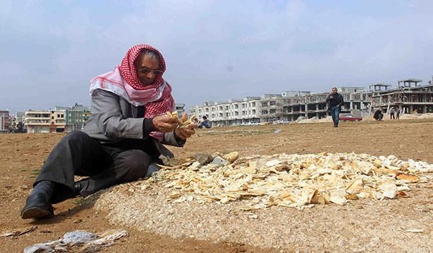 Çöpten ekmek toplayıp kuşları besliyor